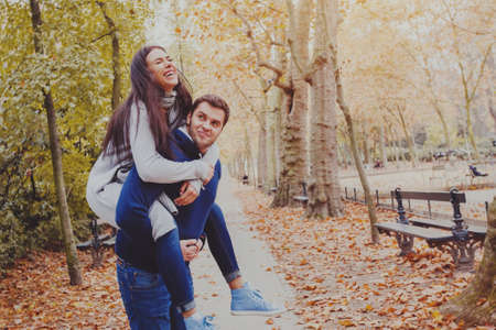 man carrying woman piggyback, dating, young couple laughing in autumn park