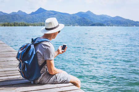 Viajero turístico con teléfono móvil, aplicación de teléfono inteligente para viajar.