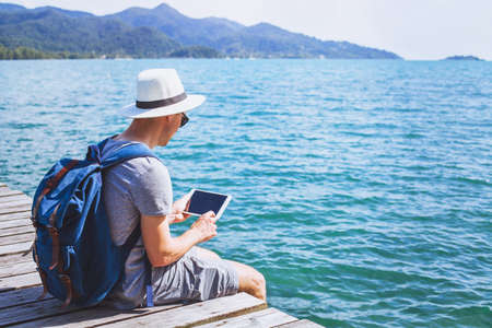 traveler using digital tablet computer while sitting on wooden pier, travel app online, man backpacker with wireless device Stock Photo