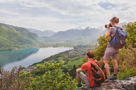 travel and tourism, couple of travelers with backpacks enjoying panoramic view of lake, hikers relaxing on top of mountain Zdjęcie Seryjne