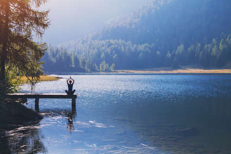 yoga beautiful background, harmony in life, meditation practice, silhouette of woman sitting in lotus position on the pier of lake and doing breathing exercises in beautiful landscape Stockfoto