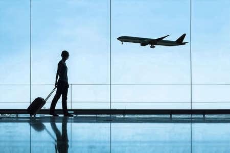 silhouette of woman in airport traveling with luggage suitcase, travel and tourism concept, airplane tickets Foto de archivo