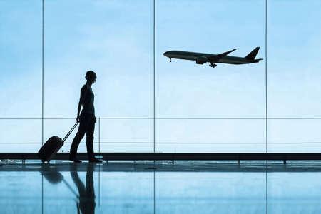 Silhouette einer Frau am Flughafen, die mit Gepäckkoffer, Reise- und Tourismuskonzept, Flugtickets reist Standard-Bild