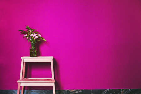pink color in interior design decoration, painted wall and vase with flowers
