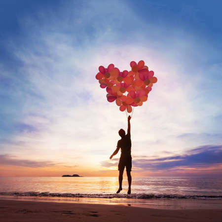Kindness and love concept, child flying with heart from balloons. Archivio Fotografico