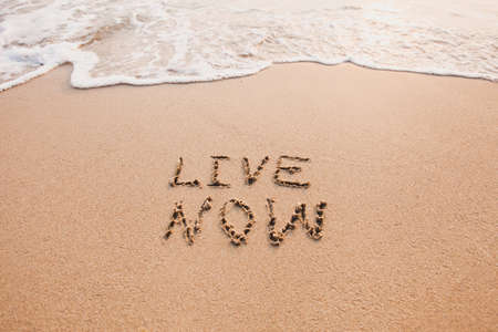 live now, mindfulness concept, text written on the sand