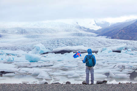 travel to Iceland, tourist in Jokulsarlon glacier lagoon holding icelandic flag, backpacker trip