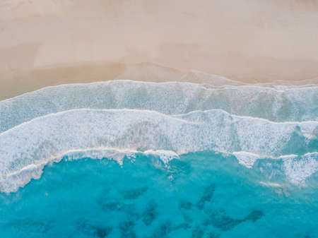 Aerial view of sand beach, ocean texture background looping, top down view of sea waves by drone. Standard-Bild