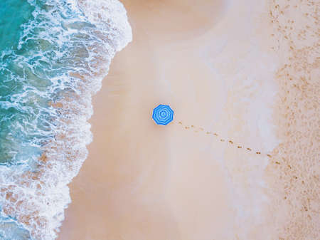 creative colorful shot of beach umbrella near ocean wave from above, minimalist landscape 版權商用圖片