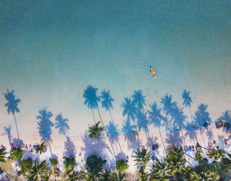 paradise beach with kayak, aerial landscape of beautiful tropical sea and palm trees, top down view from drone