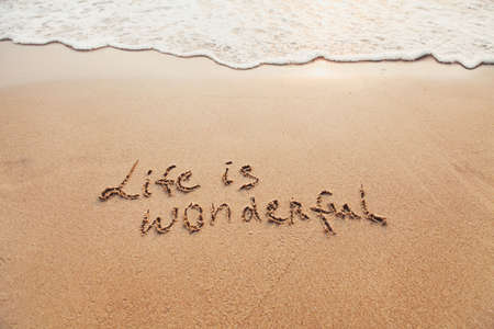 Life is wonderful, positive thinking concept. Inspirational quote written on sand.