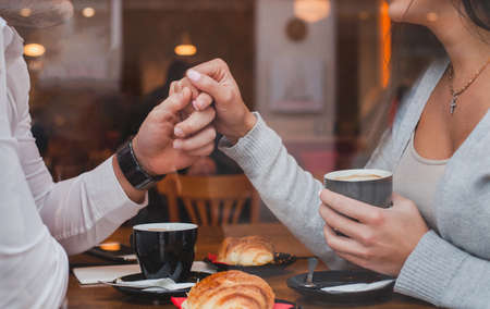 dating, romantic date in restaurant for couple, man and woman holding hands 版權商用圖片
