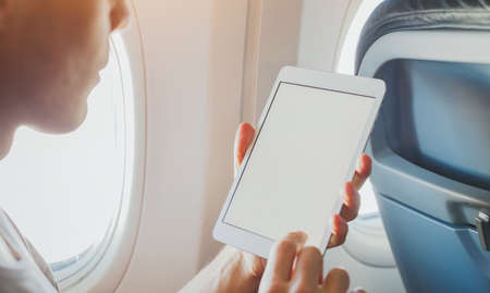 passenger using digital tablet computer in airplane,  wifi internet access on the plane, banking or reading email on screen
