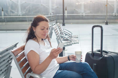 travel app, woman using mobile smart phone in airport, passenger waiting in gate terminal or railway station