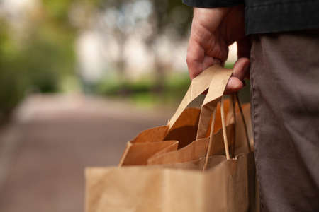 plastic free shopping concept, hand holding paper bags closeup