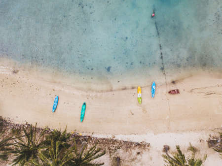aerial view of beautiful tropical island beach, top down landscape with blue sea, white sand, exotic palm trees and kayaks