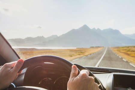travel by car, road trip adventure, hands od driver on steering wheel in sunny day Stock Photo