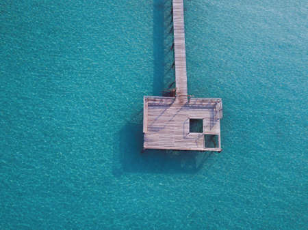 Maldives pier on tropical beach with turquoise water, vacation getaway, top down view by drone with copyspace 版權商用圖片