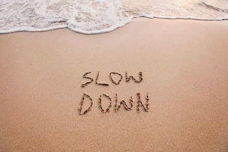 slow down, mindfulness concept written on sand
