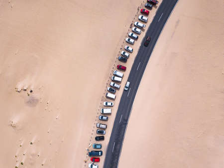 car parking lot near the road in desert, aerial top down view landscape from drone