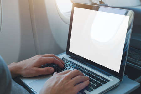 passenger using laptop computer in airplane, onboard wifi internet connection in flight, white empty screen 版權商用圖片
