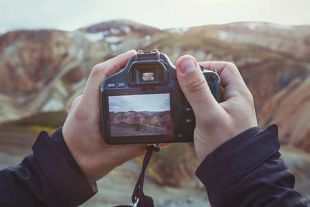 landscape travel photographer hands holding camera, taking photo of mountains