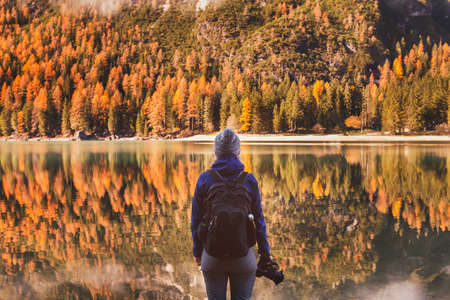 travel in autumn outdoors, photographer traveler with backpack and dslr camera standing near mountain lake