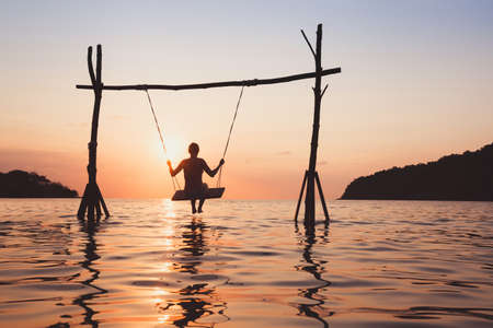 beach vacation on the sea at sunset, holidays on paradise tropical island, silhouette of woman on rope swing in water