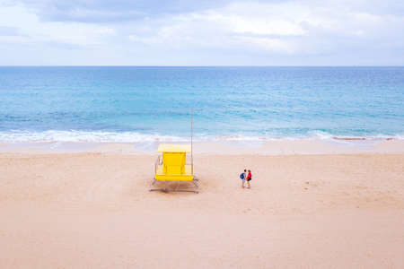 small couple in minimalist beach landscape near yellow hut and blue ocean, summer holiday travel to Canary islands