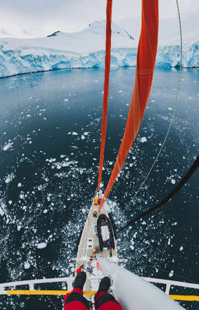 sailor standing on mast of sailing boat yacht in Antarctica, adventure travel expedition