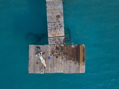 summer travel, aerial view of woman in bikini lying on wooden pier from above, beach holidays