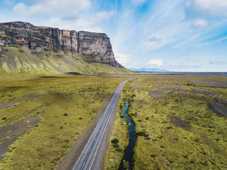 beautiful road in Iceland near big cliff, aerial view from above, South Coast
