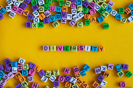 Diversity concept, word from colorful letters on yellow background.