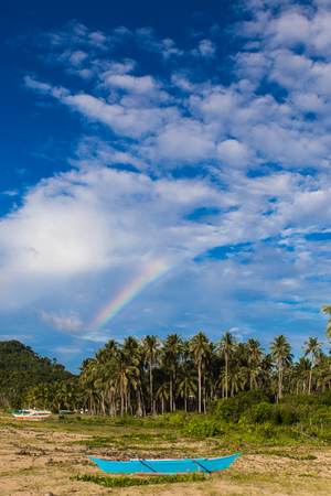 white sand beach with blue ship on foreground green palms on background, cloudy sky and rainbow in Philippines
