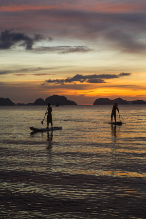 two man silhouette standing on sup boards on sunset time in El Nido, Palawan, Philippines, Corong Corong beach Imagens