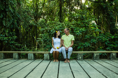 young family couple sitting at the jungle cement road with yellow flowers in their hands Imagens