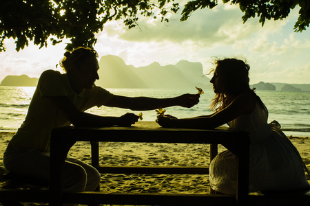young couple silhouette sitting at the table on the sunset time at the beach with yellow flowers in their hands