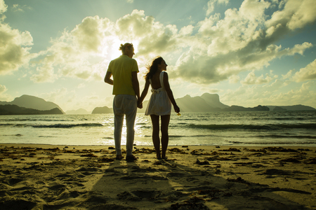 young couple silhouette on the sunset time at the beach holding their hands
