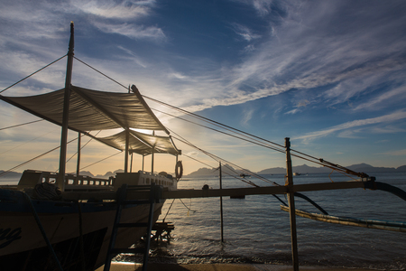 traditional philipinian boat silhouette in El Nido, Palawan with colorful sunset on background