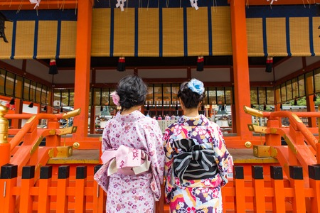 two women in geysha costumes staying behind the Fushimi Inari temple