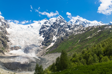Adishi glacier with blue sky on background and green trees on foreground in Georgia, Svaneti region Imagens