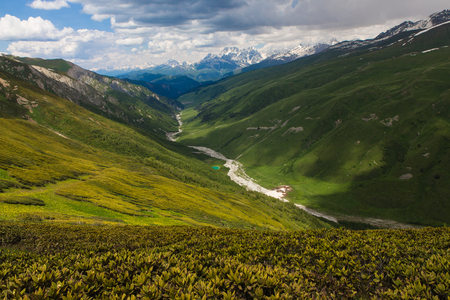 view from Chkhunderi pass to the valley and Khaldechala river in the summertime in Svaneti mountains with cloudy sky on background