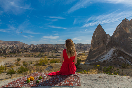 backview of woman, sitting on the carpet with Cappadocia valley on background Imagens