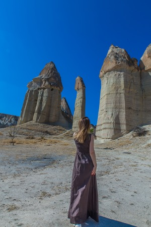 backview of women in brown dress in love valley in Turkey, Cappadocia with blue sky and sand hills in background Imagens