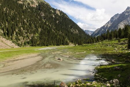 altyn arashan valley in Kyrgyzstan with green fields and wide river