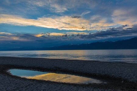 Issyk kul lake with mountains on background in Kyrgyzstan, near Karakol village Stockfoto - 131364648