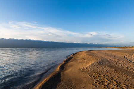 Issyk kul lake with mountains on background in Kyrgyzstan, near Karakol village