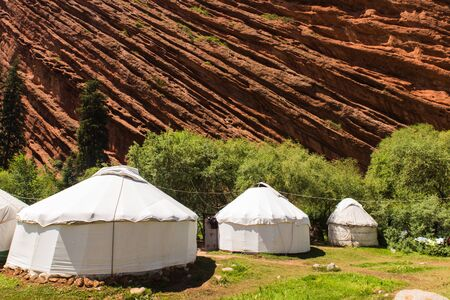 three white yurt houses at seven bulls Jeti Ogyz valley red sandstone formation in Kyrgyzstan