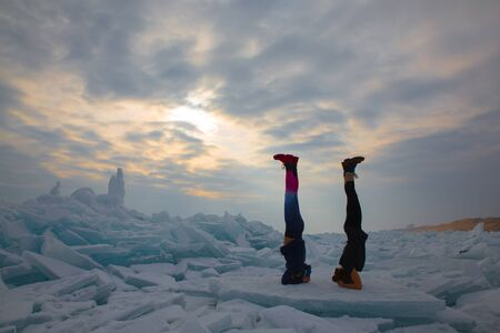 two girl in winter time doing yoga elbow stand at ice hummock in frozen lake Kapchagai near Almaty, Kazakhstan Stock Photo