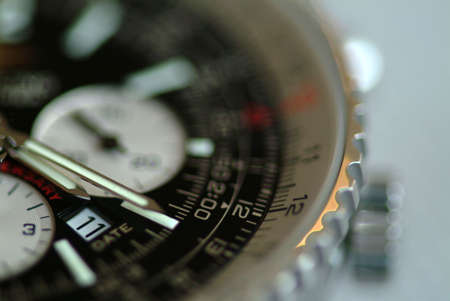 wrist: Strong shallow of field of Breitling Chronograph wristwatchs shot with focus on the date window.